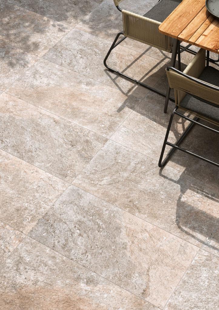 dettaglio di render di spazio outdoor con tavolo e sedie su pavimento di ceramica