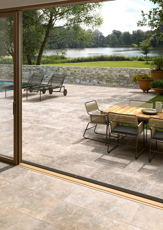render di spazio outdoor con tavolo e sedie e sdraio su pavimento di ceramica