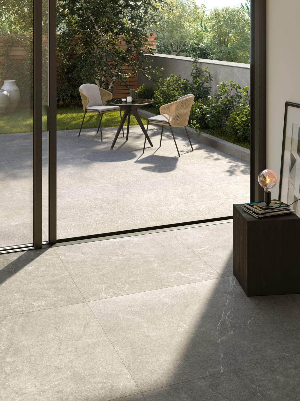 render di spazio outdoor con tavolo e sedie su pavimento di ceramica