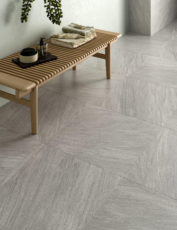 rendering di bagno con pavimento in ceramica effetto pietra e arredi moderni