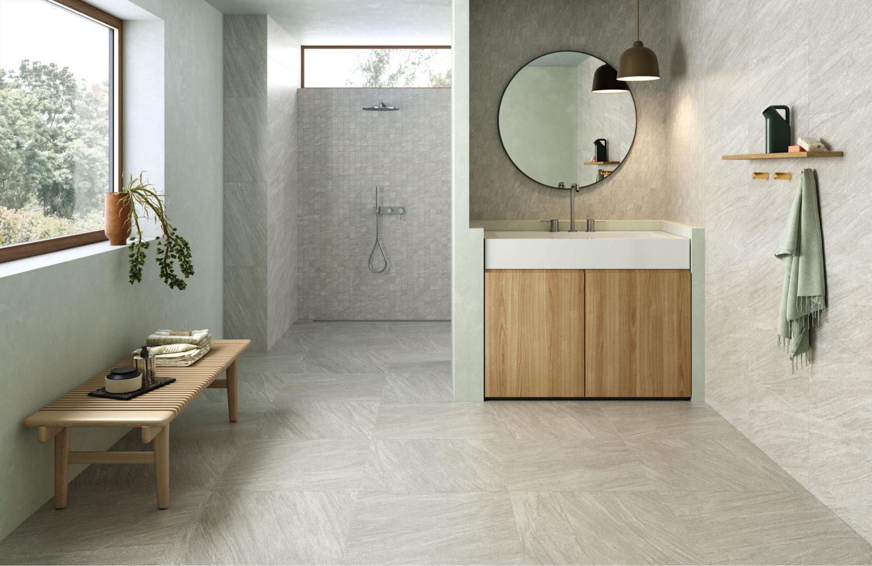 rendering di bagno con pavimento e rivestimento in ceramica effetto pietra e arredi moderni