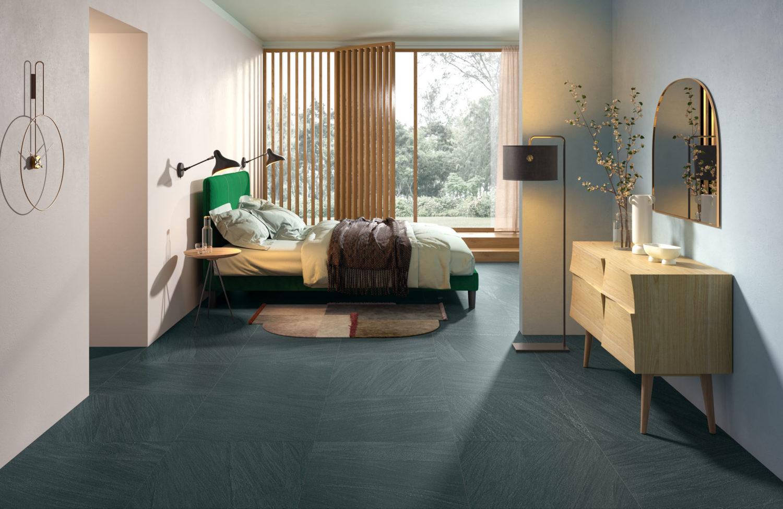 rendering di camera con pavimento in ceramica effetto pietra e arredi moderni