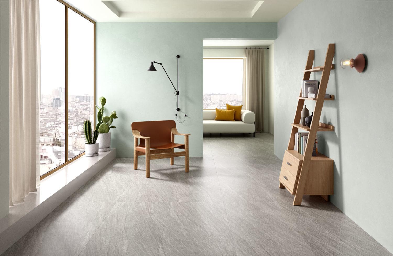 rendering di soggiorno con pavimento in ceramica effetto pietra e arredi moderni