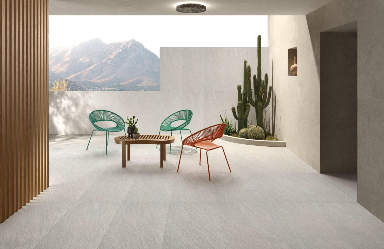 rendering di outdoor con pavimento e rivestimento in ceramica effetto pietra e arredi moderni