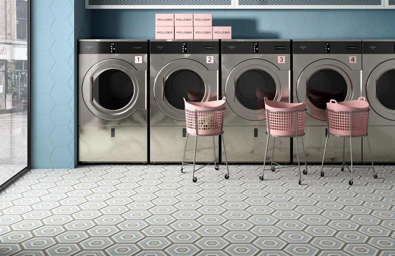 rendering di lavanderia a gettoni con pavimento di piastrelle esagonali decorative e cesti per la biancheria su ruote e lavatrice