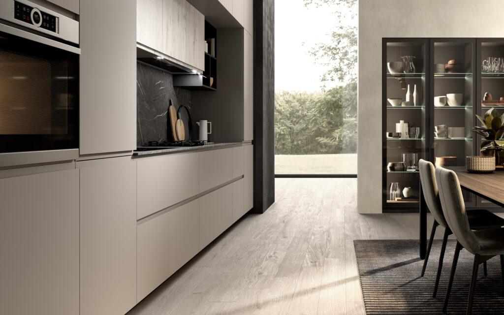 rendering di cucina di gusto contemporaneo con inquadratura con composizione sulla sinistra e tavolo e sedie sulla destra