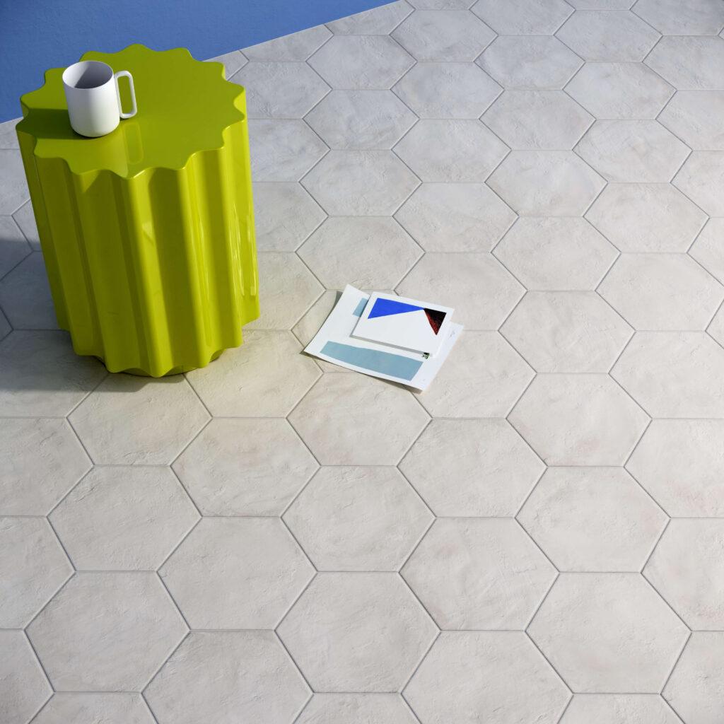 rendering con dettaglio di pavimento di esagone colore chiaro in ceramica e tavolinetto con tazza