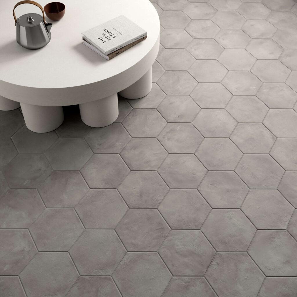 rendering con dettaglio di pavimento di esagone colore scuro in ceramica e tavolinetto con alcuni oggetti